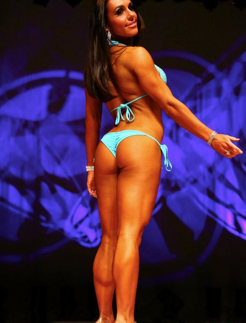 Alyssa Michelle Agostini showing her back, glutes, and legs to the judges in front of the stage