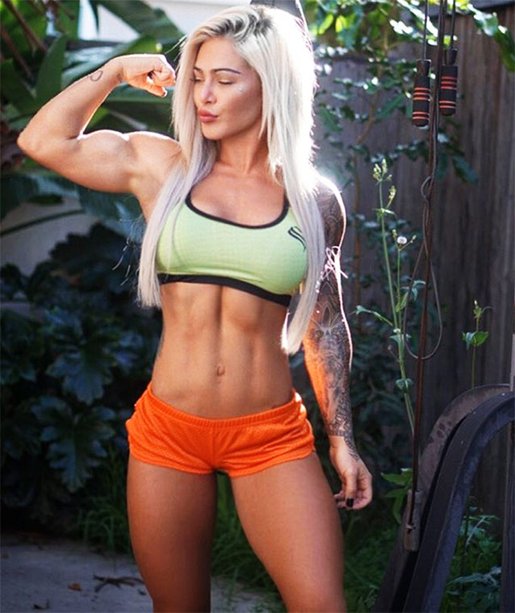 Badass Cass Fit tensing her biceps, displaying her muscular definition and size.