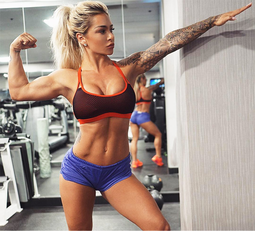Badass Cass Fit tensing her biceps in the gym, posing for the camera, and also displaying her abs.