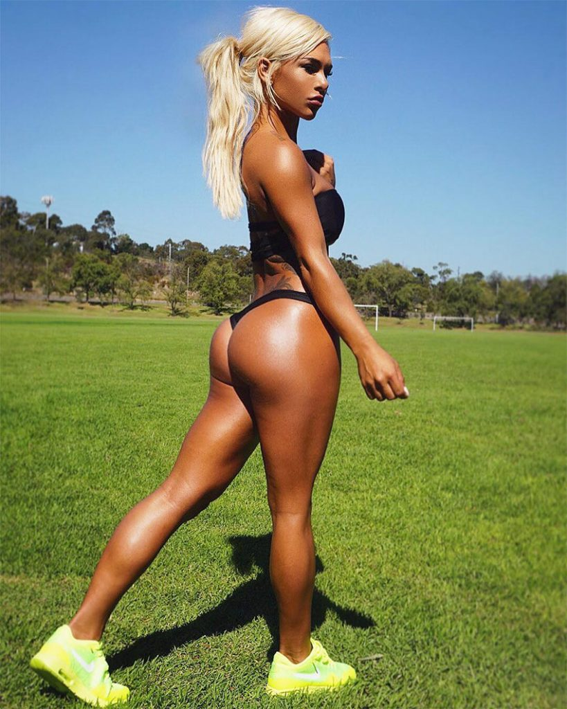 Badass Cass Fit posing on a soccer pitch in a bikini, displaying her muscular glutes and legs.