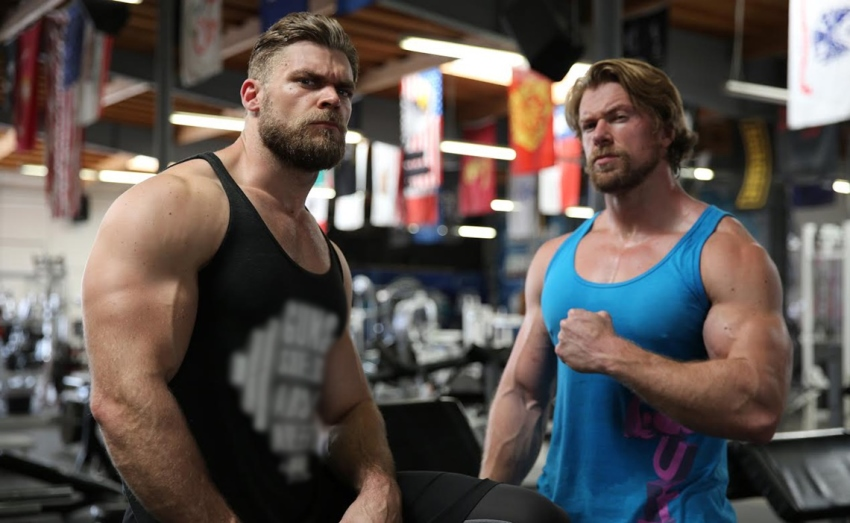 Buff Dudes flexing their arms at the camera, while at the gym in black and blue tank tops