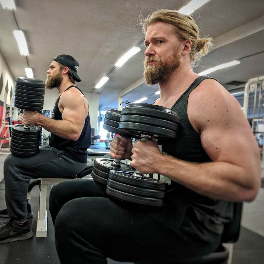 Buff Dudes preparing to do a set in the gym, sitting on a bench next to each other