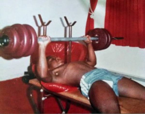 Charles Dixong completing a bench press on his first weights set as a boy