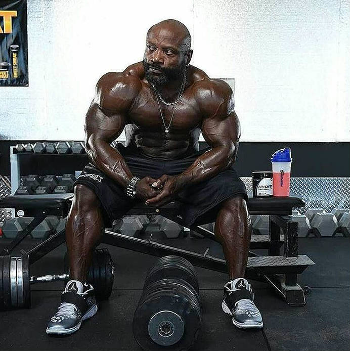 Charles Dixon sitting in front of a dumbbell