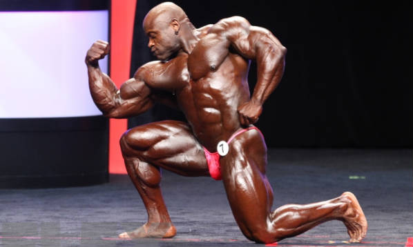 Charles Dixon posing at competition and tensing his bicep