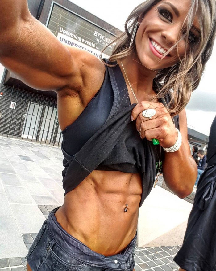 Christina Eleni pulling up her top revealing her well defined abs and smiling