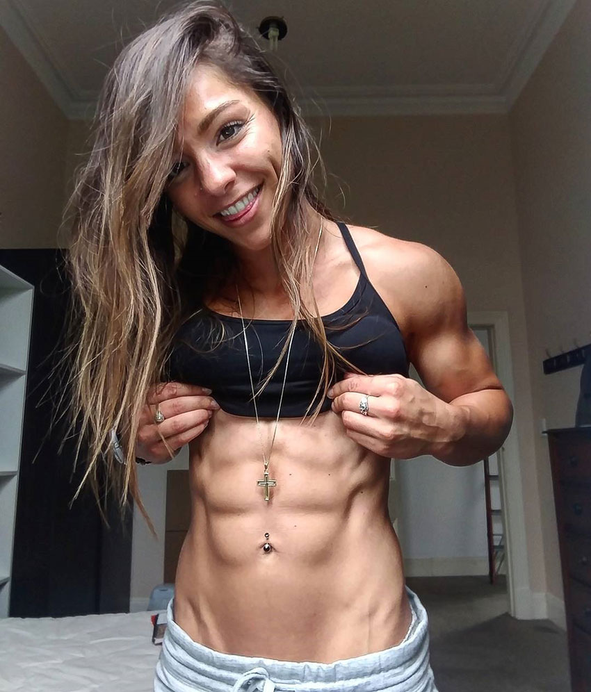Christina Eleni oulling up her top with both hands flexing her well defined abs and lean body