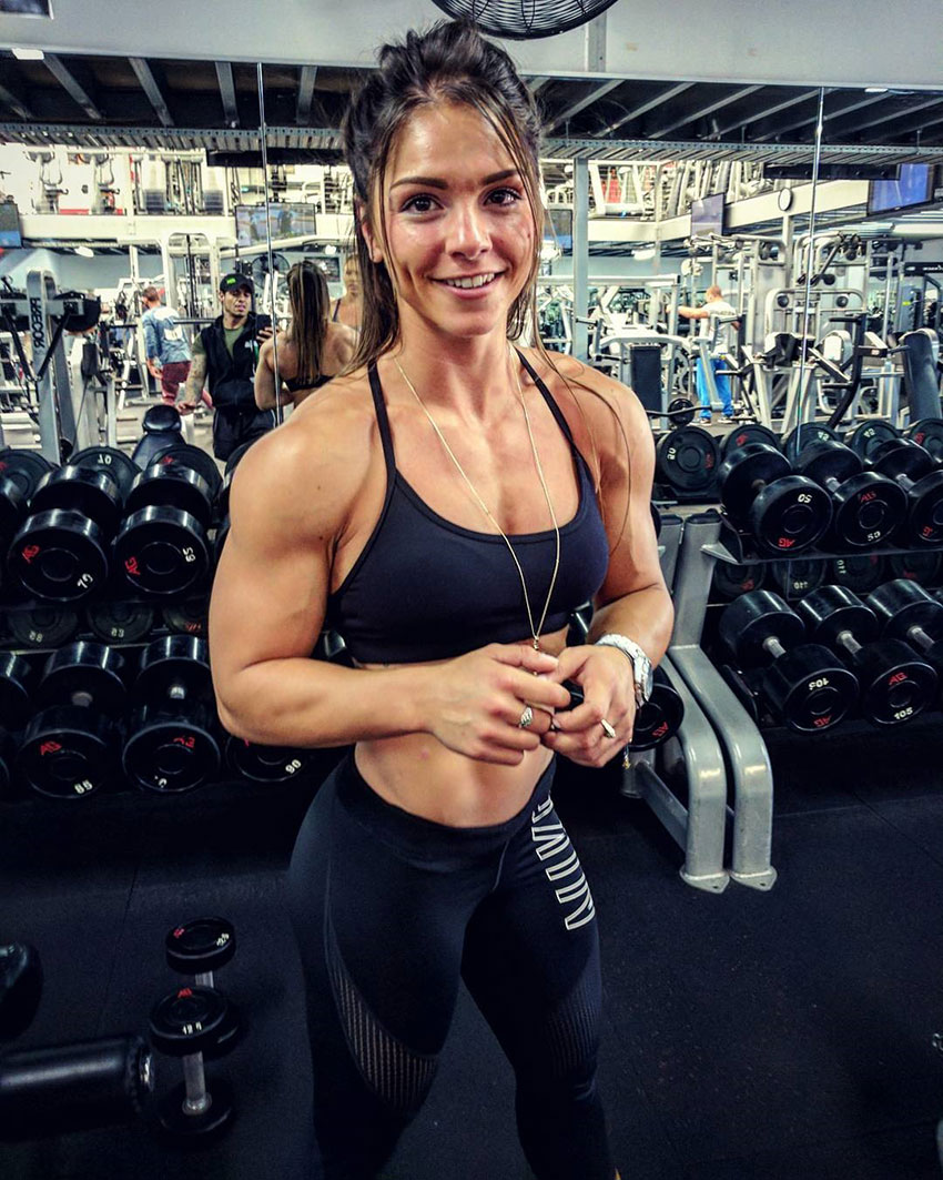 Christina Eleni standing in the gym with large biceps and shoulders wearing gym clothes looking muscular and lean