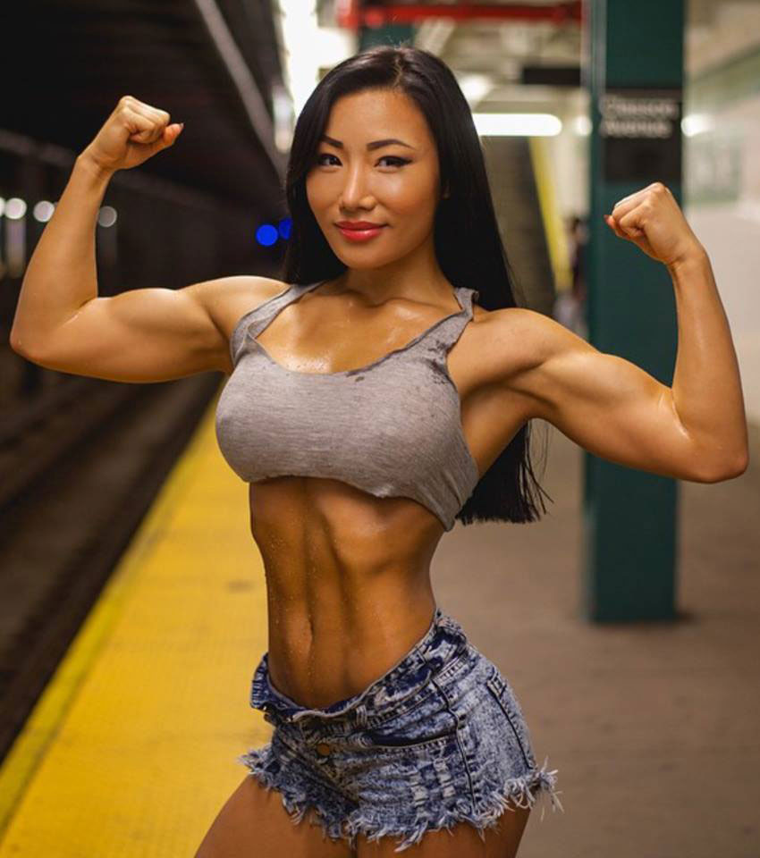 Chu mi Kim flexing both biceps in teh underground subay wearing a tight top and showing her strong abs