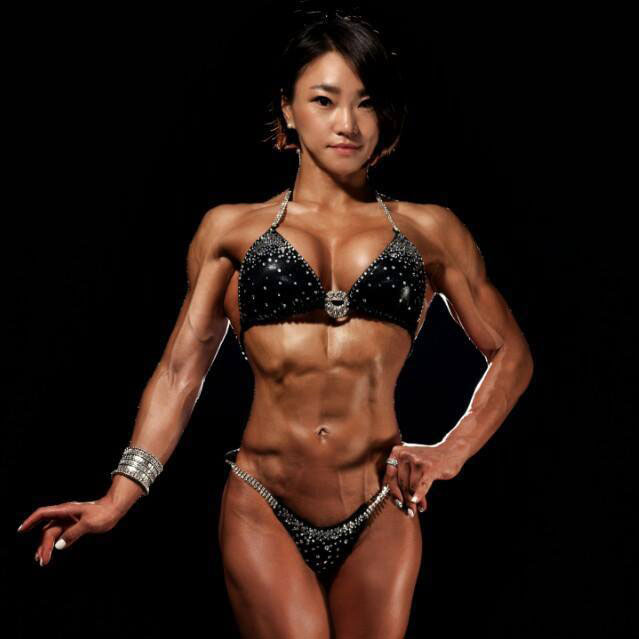 Chu mi Kim posing on a bodybuilding stage