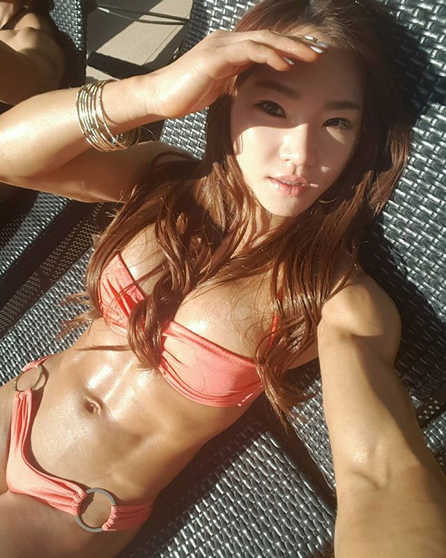 Chu mi Kim sunbathing wearing a bikini looking ripped and lean showing her abs