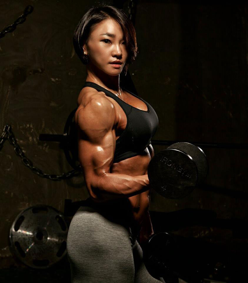 Chu mi Kim performing a bicep curl in the gym showing her huge bicep while wearing tight gym clothes