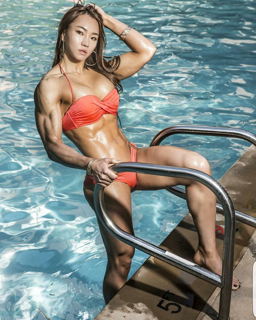 Chu mi Kim pulling herself out of a swimming pool wearing a bikini looking lean and strong