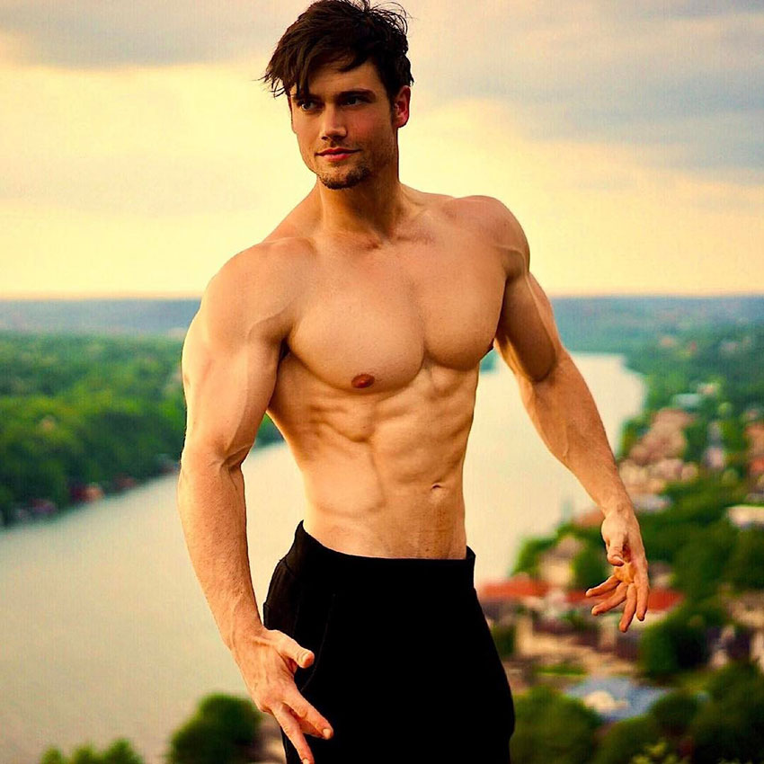 Connor Murphy standing outside shirtless flexing his abs and chest