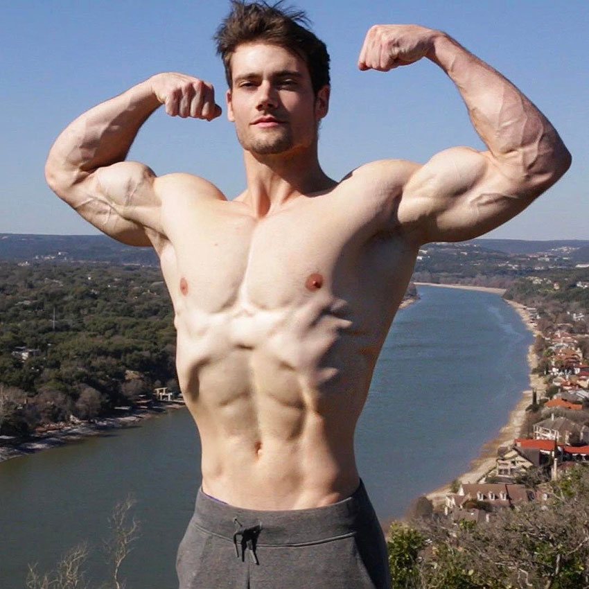 Connor Murphy standing outside with his shirt off flexing his biceps