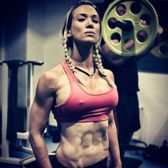 Cornelia Ritzke standing in the gym in front of the barbell