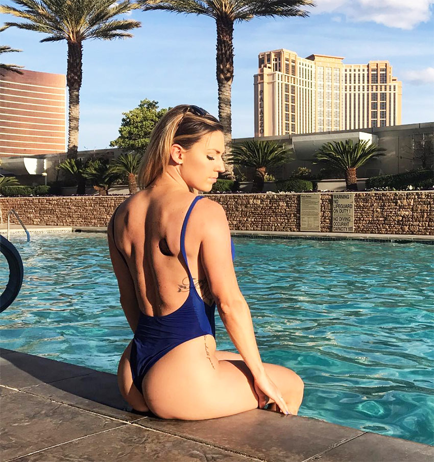 Courtney Gardner relaxing in a swimming pool in california, showing the muscular definition on her back.