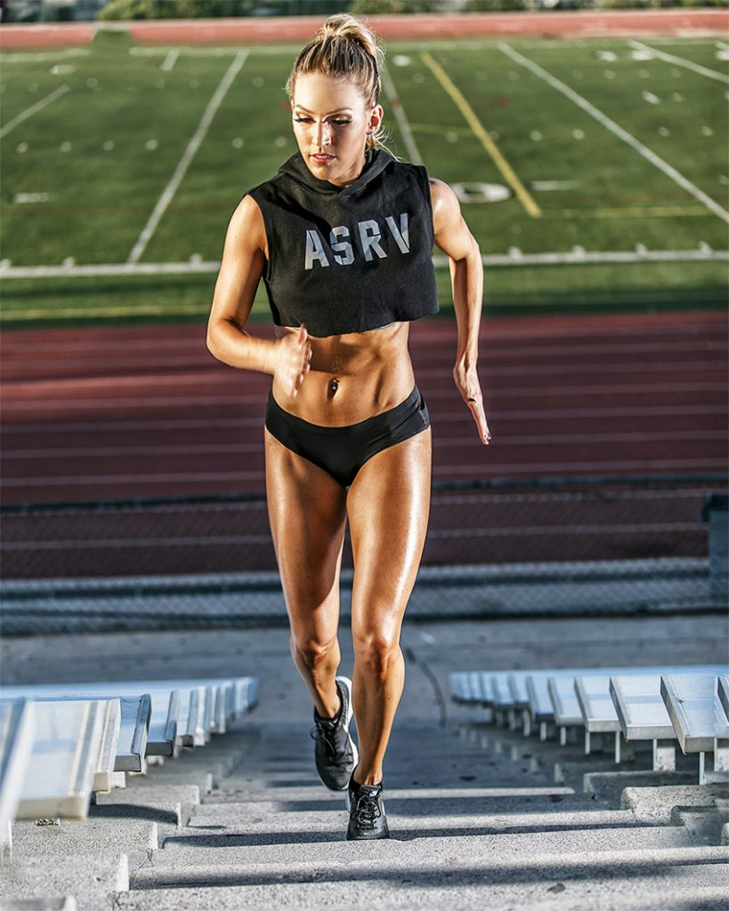 Courtney Gardner training on the steps of a track and field stadium in sportswear, displaying her lean and muscular figure.