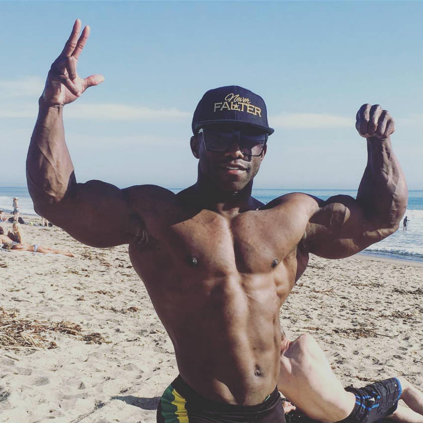 Damion Ricketts standing on the beach and tensing his biceps