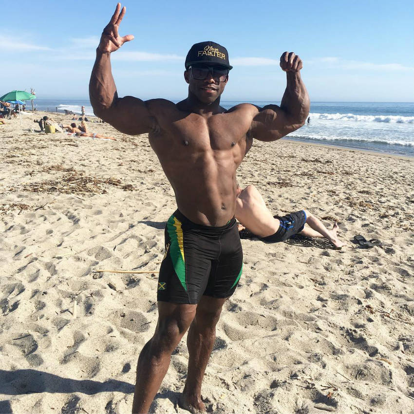 Damion Ricketts standing on the beach showing his full body and tensing his biceps