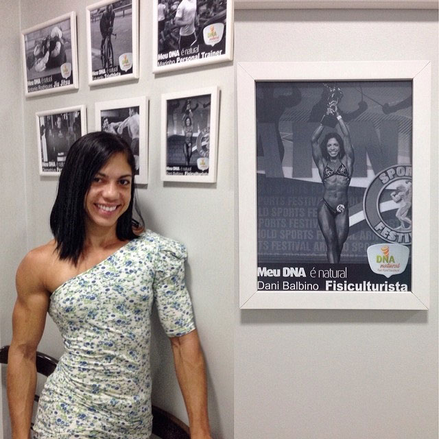 Dani Balbino wearing a white dress standing next to her own picture n the wall highlighting her bodybuilding competition achievements