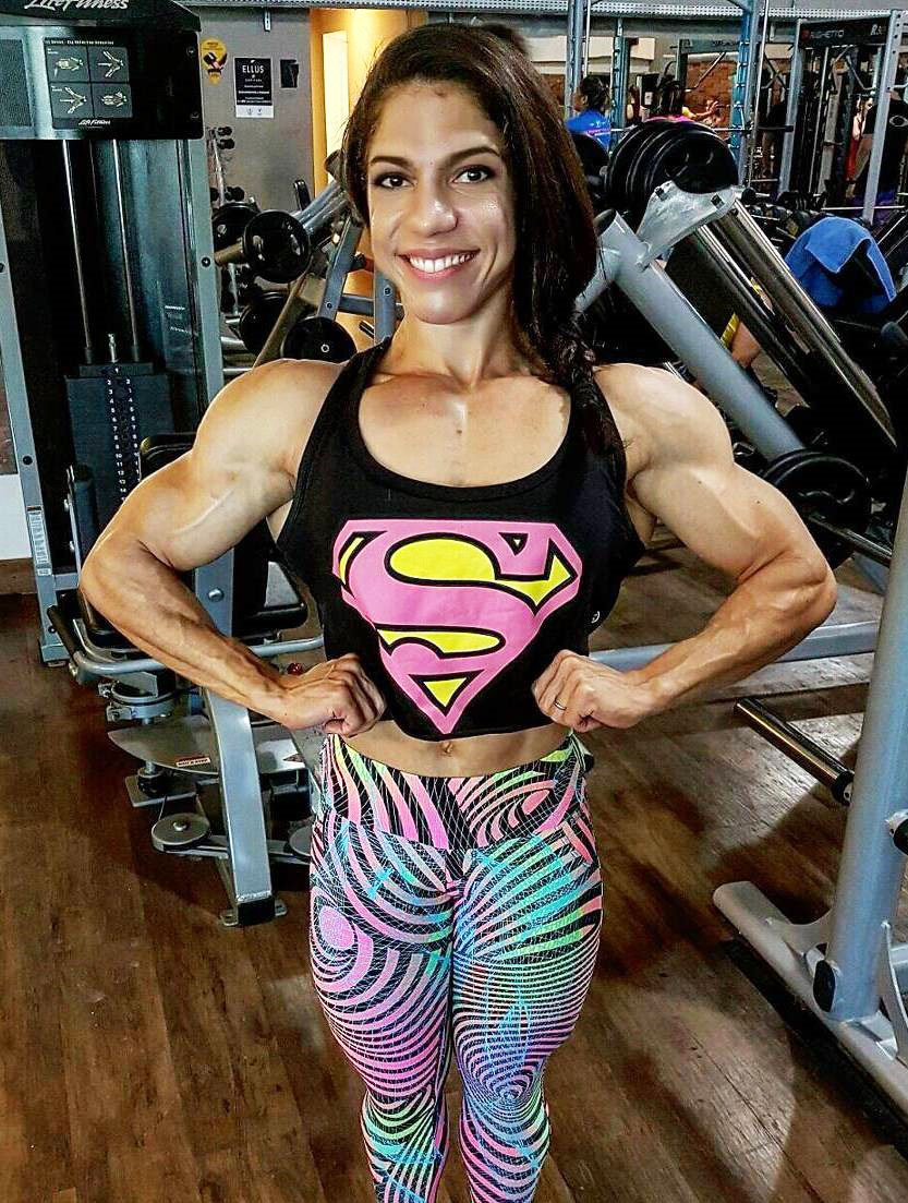 Dani Balbino standing in the gym flexing both of her biceps and chest