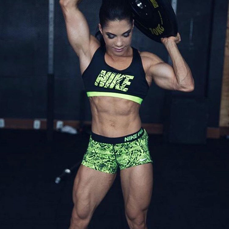 Dani Balbino holding a weight over her head looking strong and ripped