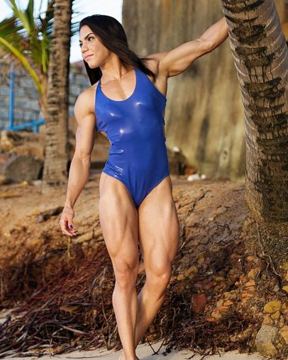 Dani Balbino standing next to a tree wearing a blue swimsuit looking strong and lean