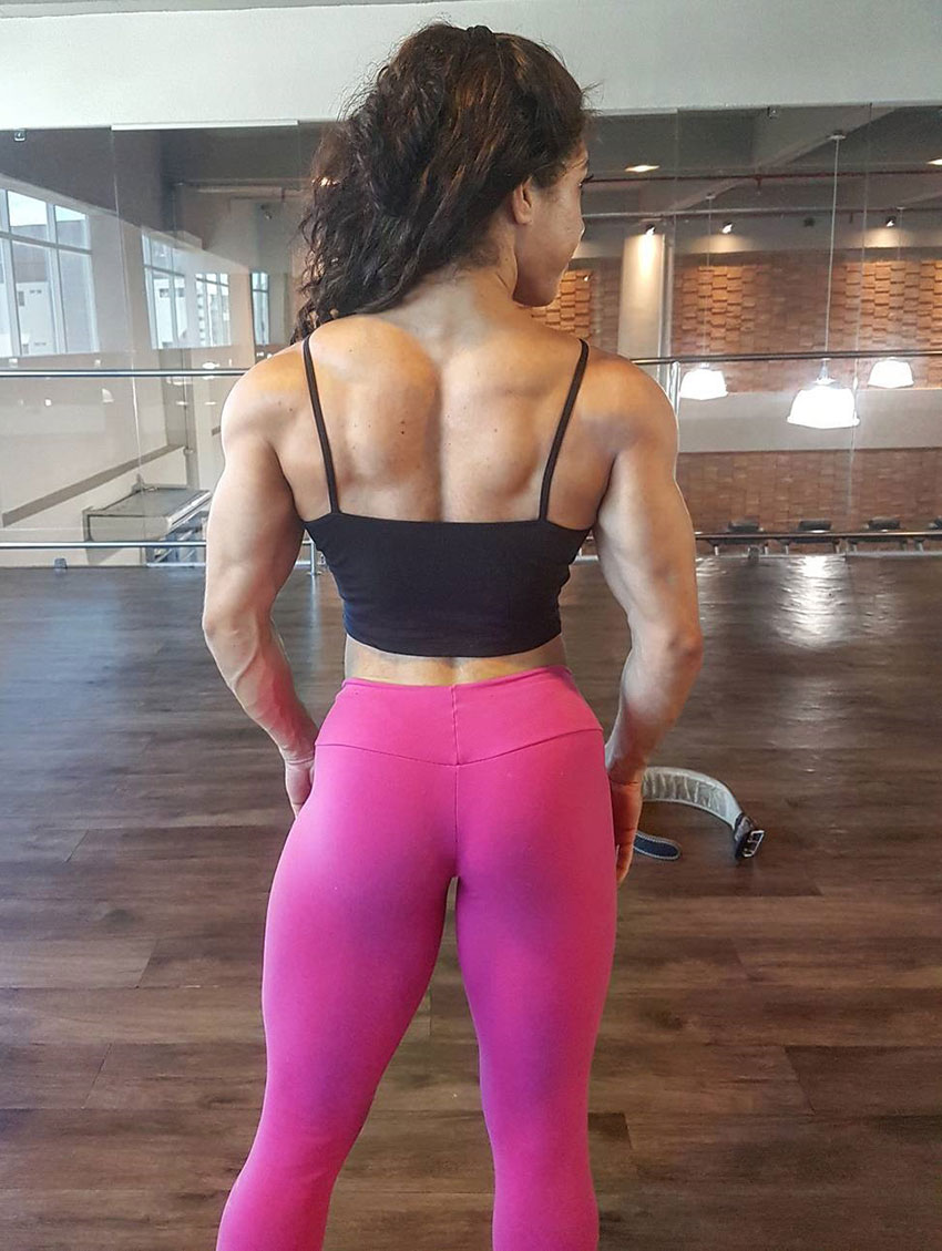 Dani Balbino showing her back and glutes to the camera in teh gym