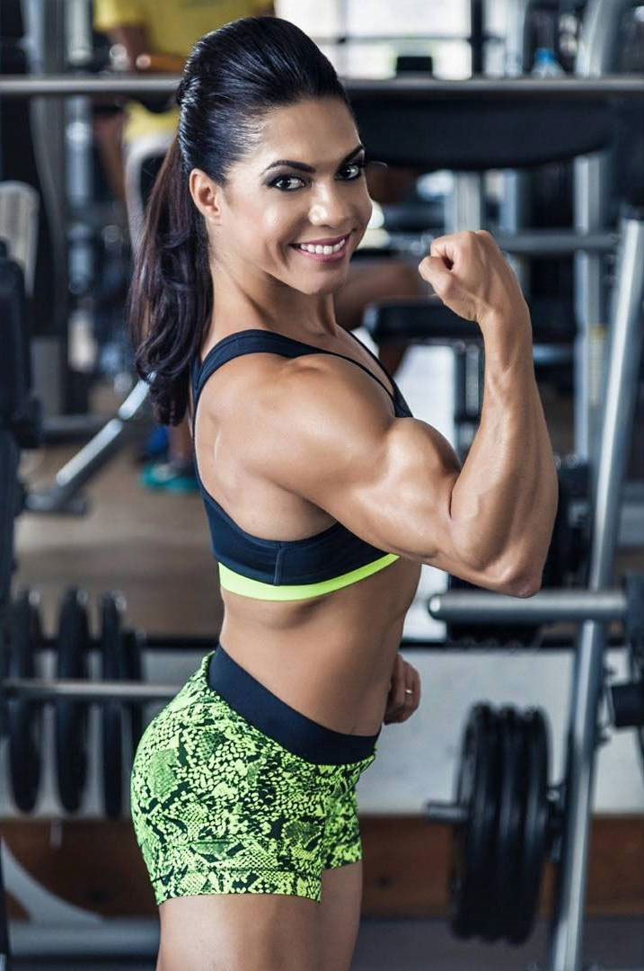 Dani Balbino standing in the gym smiling flexing her right bicep