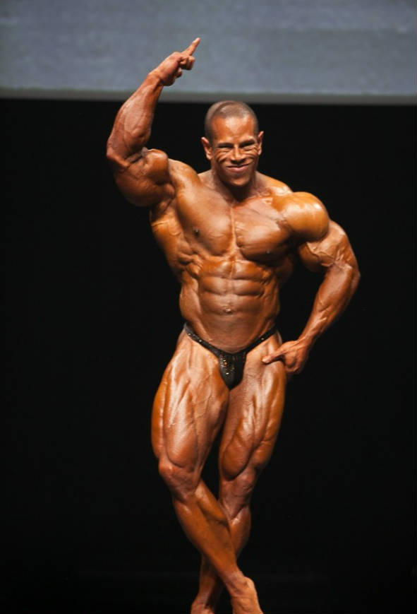 David Henry posing at a competition with his finger in the air