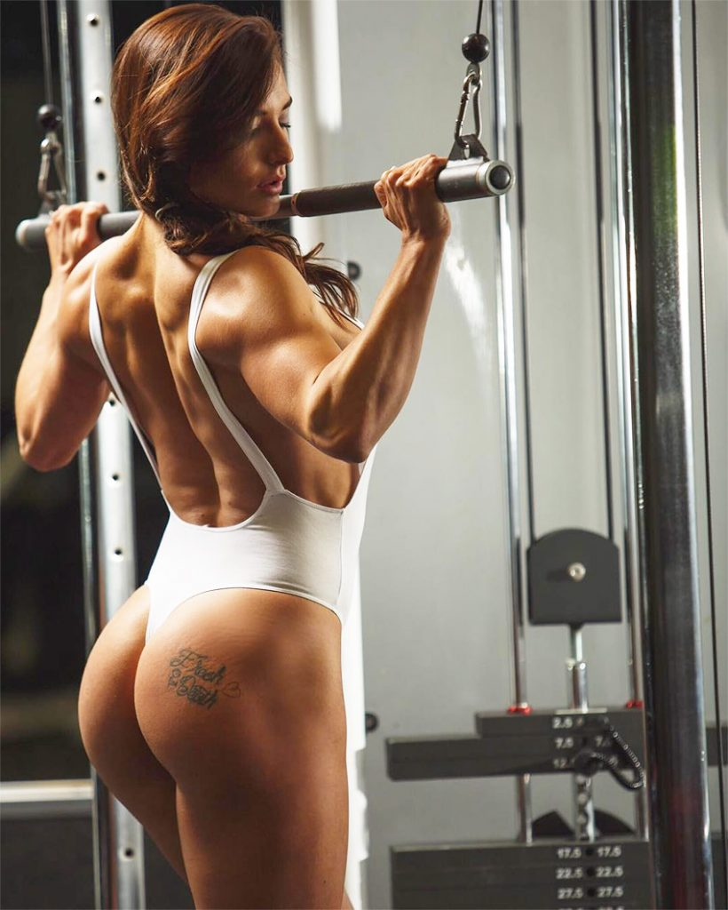 Emeri Connery pulling down a weight on a cable machine in a bikini, showing her impressive muscular back and incredibly sculpted glutes and legs.