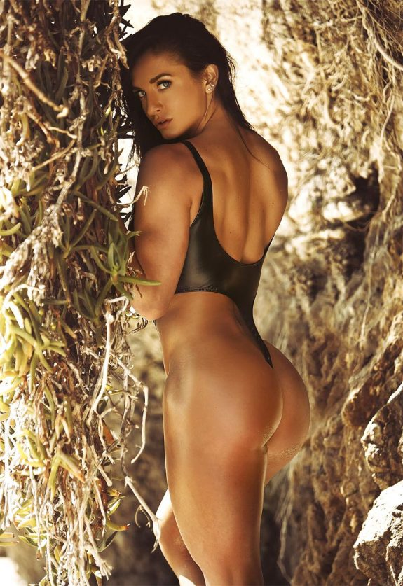 Emeri Connery during a professional photoshoot for her profile on Instagram, posing showing her impressive glutes, legs and back in a black full-body bikini.