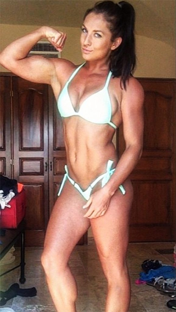 Emeri Connery posing in a white bikini in 2015, tensing her biceps and abs.