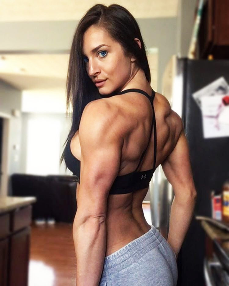 Emeri Connery tensing her back and posing to show her muscular definition in her kitchen.