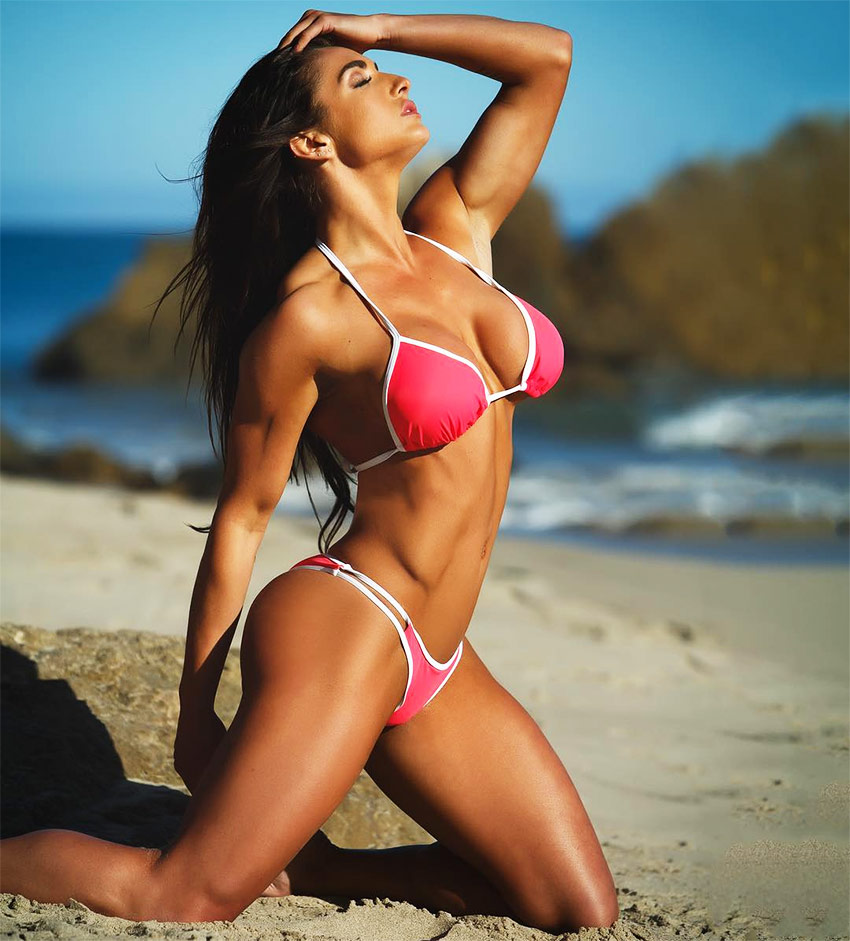 Emeri Connery posing on the beach in a pink and white bikini, kneeling on the sand while showing her muscular definition.