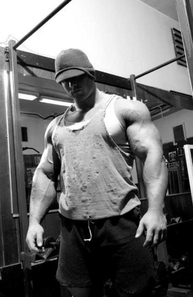 Frank Mcgrath stands in a darkened gym room wearing a ripped vest