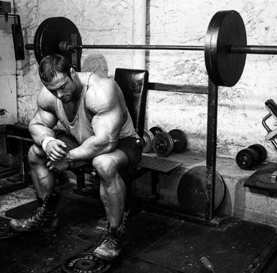 Frank Mcgrath sitting in the gym on a bench in front of the barbell