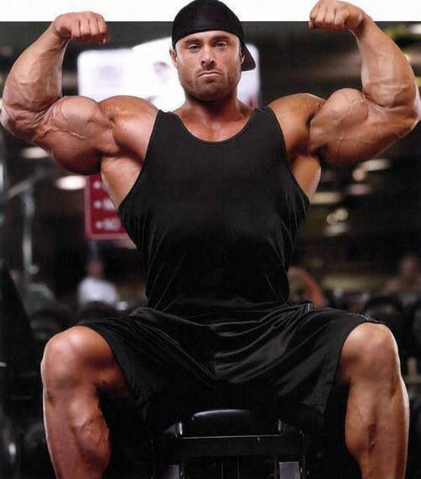 Frank Mcgrath tenses his biceps and looks straight at the camera