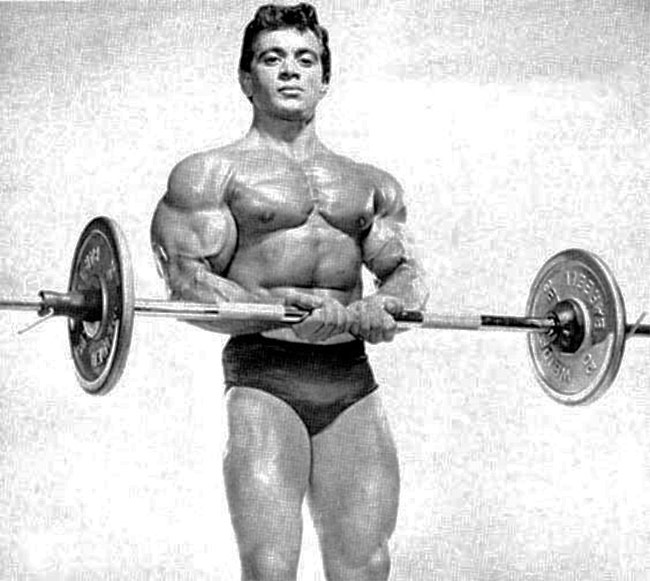 Freddy-Ortiz-holding-a-barbell-and-flexing-for-a-photo