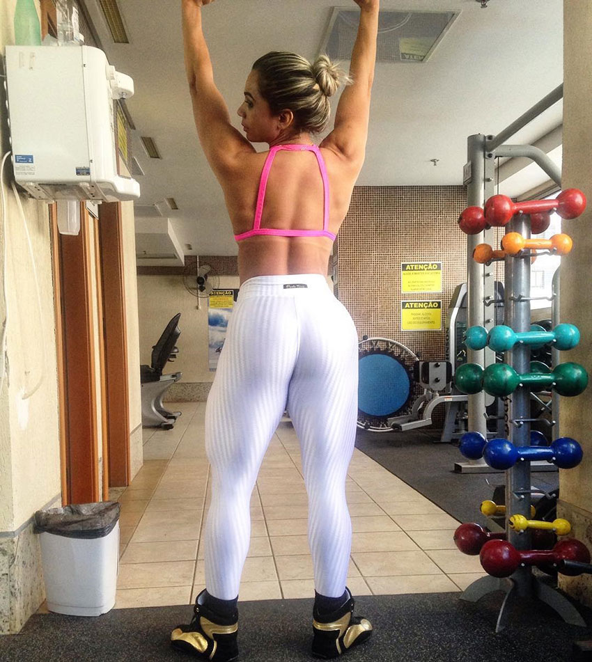 Gleycelilia Bracca flexing her back and rams in the gym while stretching towards the sky, while also showing her large leg, and glute muscles.