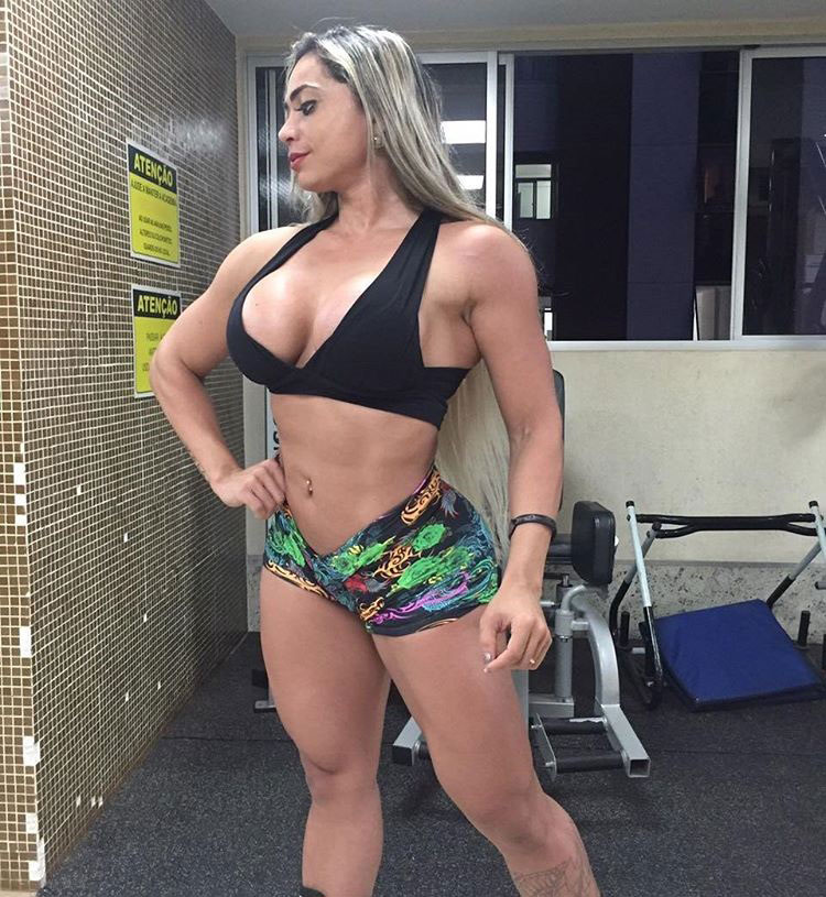 Gleycelilia Bracca standing in the gym wearing short shorts, and a tight top flexing her legs, abs, and biceps as if practicing for a bodybuilding show