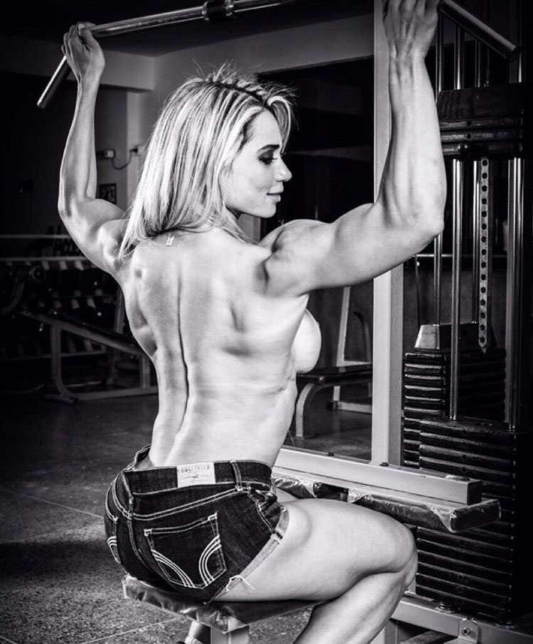 Gleycelilia Bracca performing a lateral pull down in the gym showing her large back, and arm muscles
