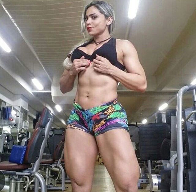 Gleycelilia Bracca flexing her abs in the gym while wearing short shorts and a tight black top