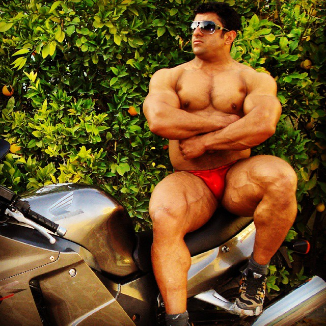 Hadi Choopan sitting on a motorbike with his arms crossed, as he shows his big and muscular physique
