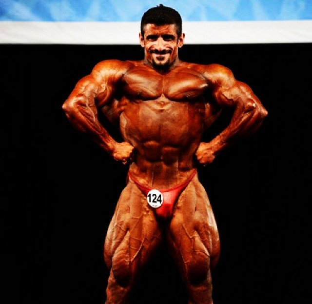 Hadi Choopan in a front lat spread pose on the stage
