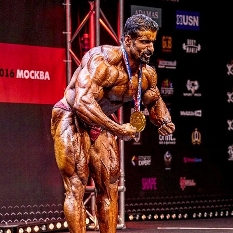 Hadi Choopan in a most muscular pose on the stage, as he shows his medal-winning physique to the audience
