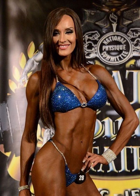 Heidi Carlsen posing on a bikini stage, showing her ripped abdominals, arms, and legs