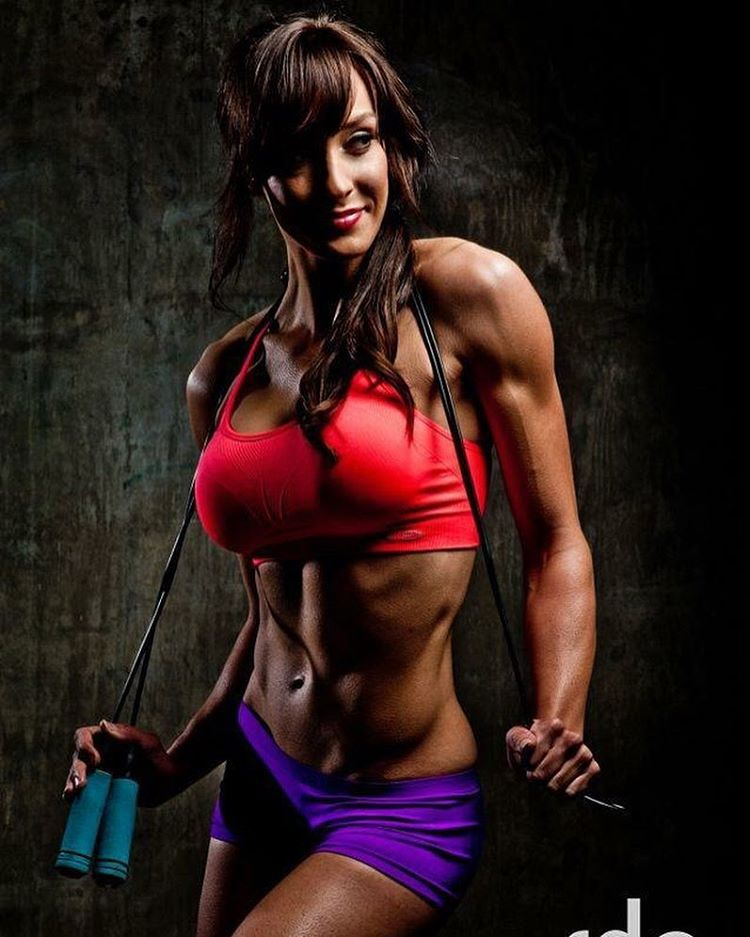 Heidi Carlsen holding a jumping rope around her neck, while posing for a photo shoot and showing her ripped body