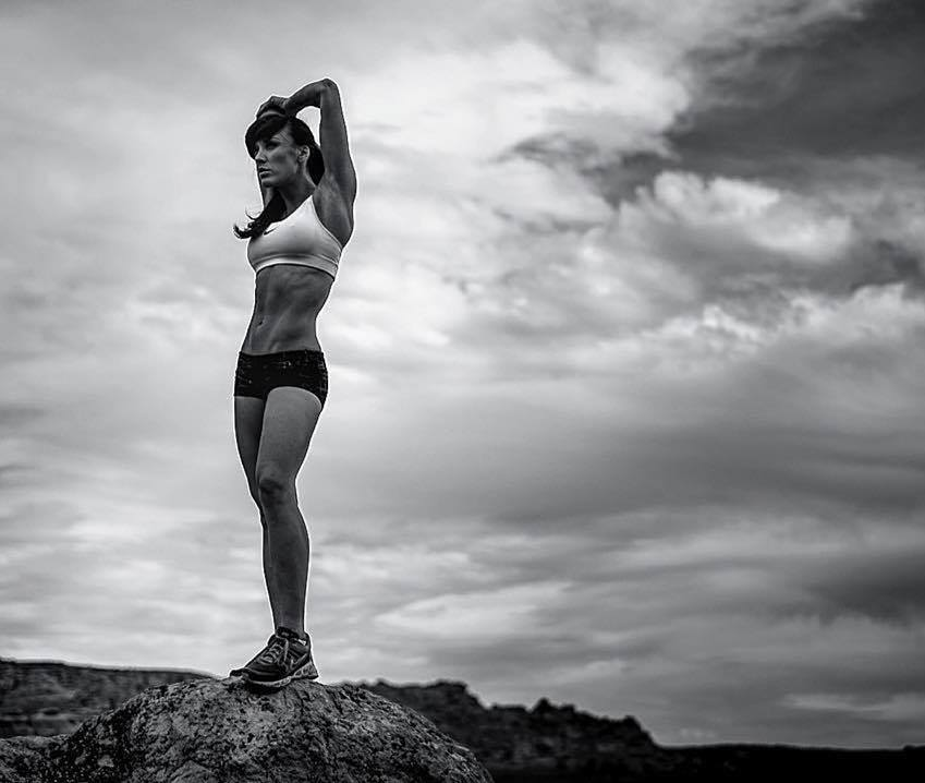 Heidi Carlsen stretching her arms and lats outdoors, standing on a rock